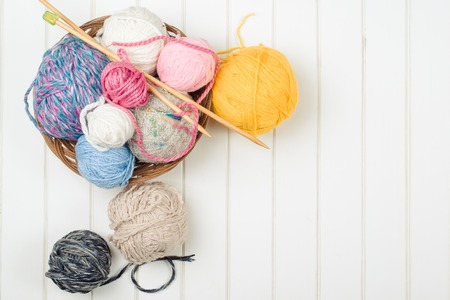 Knitting yarn balls and needles on the white wooden background.
