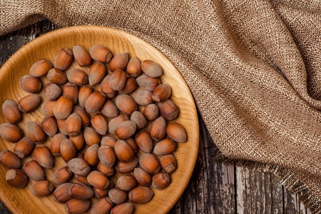 avellanas: Hazelnuts in a wooden bowl on the dark background.