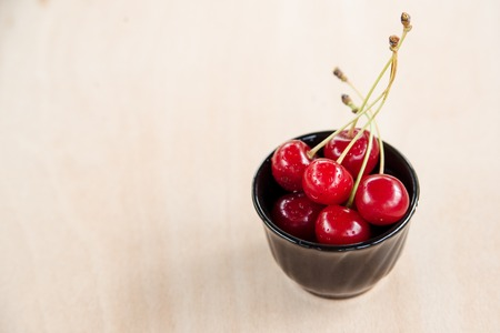 Fresh cherry in a bowl on the table.