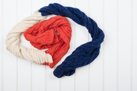 mauve: Colorful woolly hat and scarf on the white wooden background.