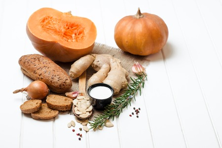 Pumpkin and ingredients for cooking over the white wooden background. Vegetarian food, health or cooking concept. Stock Photo