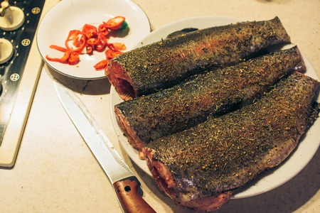 brown trout: Fresh trout with spices and seasoning on the cutting board.