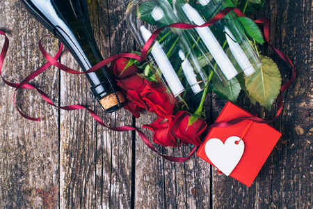wine gift: Valentines day cards. Bouquet of red roses, two glasses, bottle of wine, gift box with tag on vintage wooden board. Vintage toned.