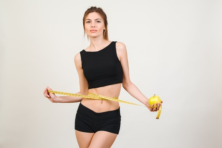 Young beautiful brunette woman measuring her waist with a measure tape isolated on a white background. Stock Photo