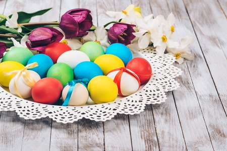 Easter background. Colored easter eggs and spring flowers on the white wooden background.
