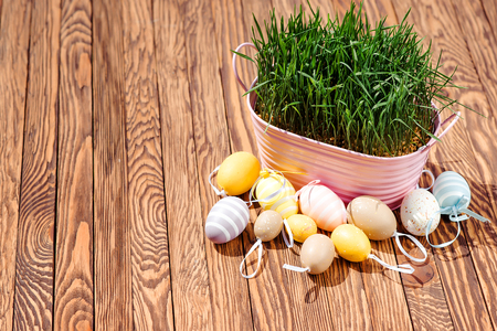 celebratory event: Decorated easter eggs, pink bowl with green grass on the wooden background. Space for text. Stock Photo