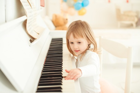 Cute little girl playing piano in a light room. Stock Photo