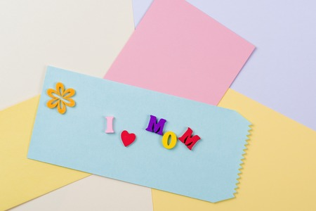 spelled: Mothers Day concept. I love mom spelled with colorful wooden letters on the paper background.