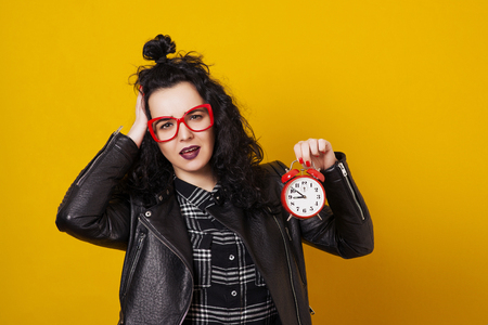 Beautiful surprised young woman with alarm clock standing in front of a yellow background. Stock Photo