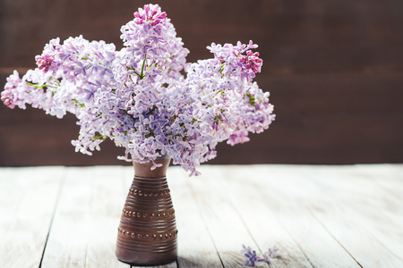 The beautiful lilac on the wooden background.