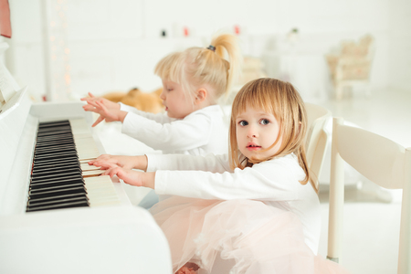 luxury apartment: Two cute little girls playing piano in the studio. Stock Photo