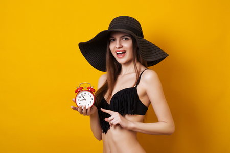 Beautiful young woman in black swimsuit and fashionable hat with alarm clock standing on the summer yellow background.