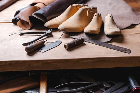 Leather in rolls, cobbler tools and shoe lasts in the workshop. Leather craft tools.