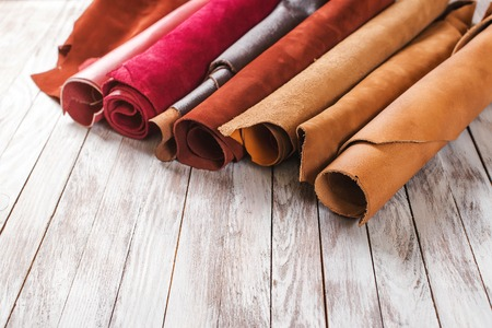 Multicolored leather in rolls on the wooden background.
