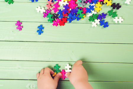 segmented bodies: A lot of puzzles on the wooden table. Child connects puzzles. Stock Photo