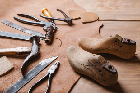 Cobbler tools in a workshop on the wooden table .
