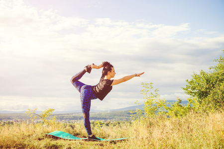 Young woman doing yoga or fitness exercises outdoor, nature landscape at sunset. Stock Photo