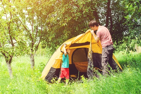 pitching: Happy father with son putting up tent together in woods.