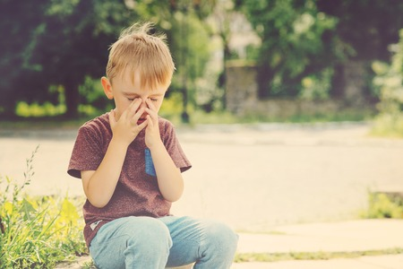 capricious: Little kid boy 4-5 years old crying on summer walk.
