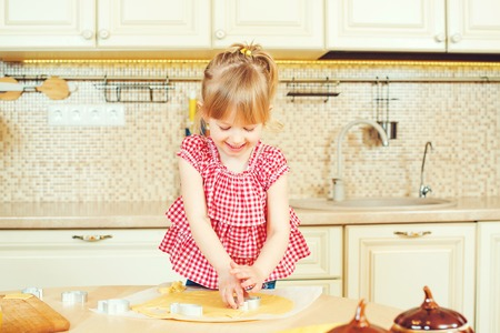 Cute little girl helping her mother bake cookies in the kitchen.