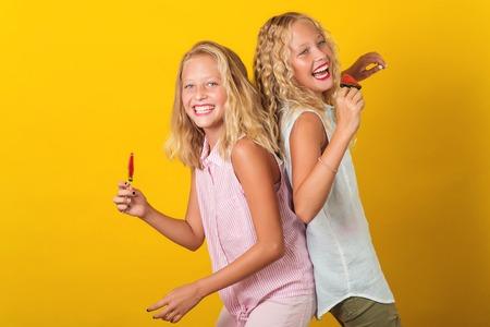 Zwillingsjugendlichmädchen, die Spaß zusammen, lokalisiert auf dem gelben Hintergrund haben.