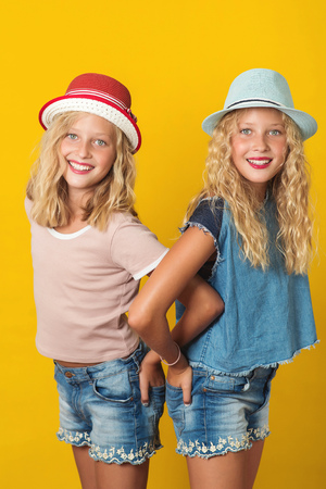 Portrait of handsome young twins girls in summer hats, posing on the yellow background.