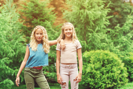 Portrait of beautiful teenager girls twins at park, lifestyle people concept.
