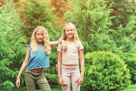 Portret van de mooie tweelingen van tienermeisjes bij park, het concept van levensstijlmensen. Stockfoto
