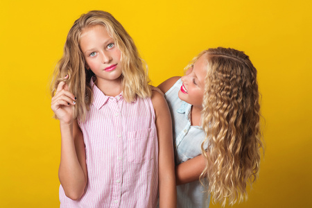 Funny girls twins have fun together on the yellow background.