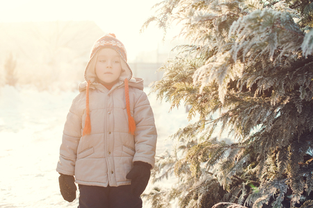 Portrait of cute boy, wearing in warm hat with pom pom in a cold winter day playing outdoor with snow.