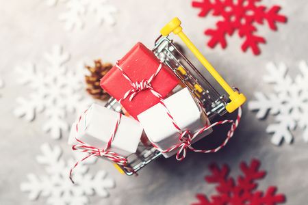 Christmas gift boxes in a shopping cart over the grey background with decorative snowflackes around, top view. Christmas sale concept. Stock Photo