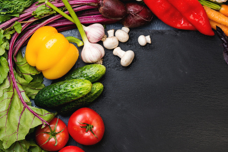 Fresh vegetables background for cooking on the dark background with space for text. Top view.