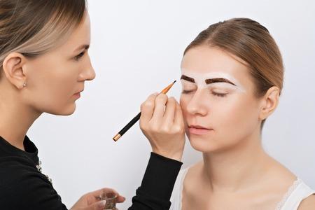 Beautiful young woman during an eyebrow correction procedure.