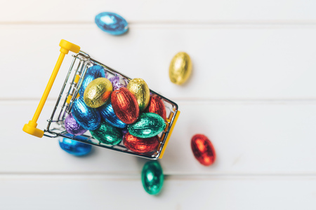 Shopping cart with colorful easter eggs on the white wooden background.