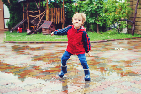 Happy boy jumping in puddles after raining.