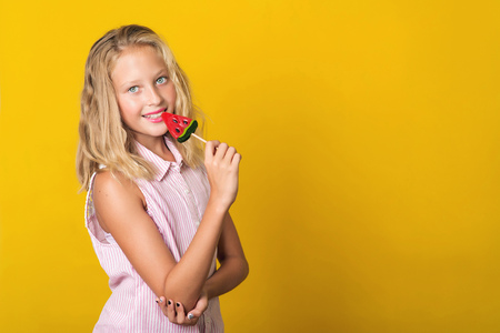 Handsome young girl having fun with lollipop over the yellow background, copy space