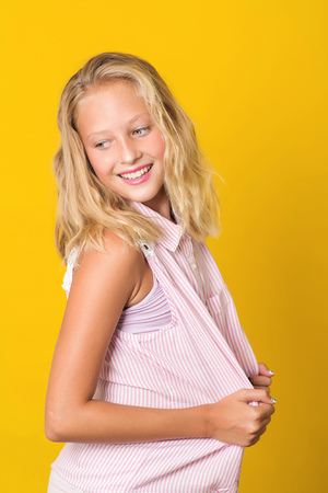Handsome young girl posing on the yellow background. Foto de archivo
