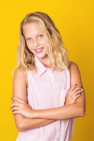 Handsome young girl posing on the yellow background. Stockfoto