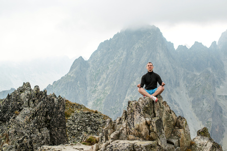 The young man sits on top of mountain in Lotus pose.