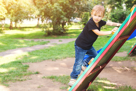 Happy little boy climbing at playground in a park.