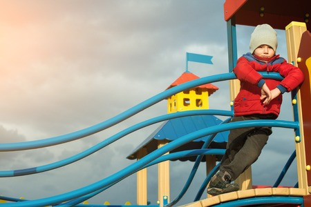 Cute boy having fun on outdoor playground in a cold weather.