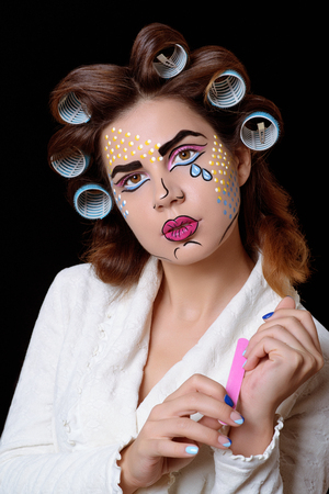 Model with pop art makeup against the black background.