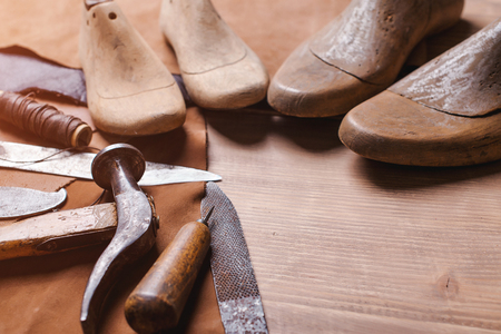 Cobbler tools in a workshop on the wooden table . Space for text.