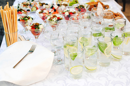 Catering for outdoors party. Catering buffet food on some festive event, party or wedding reception. Water with lemon and mint. Greek salad in glasses on table, banquet food. Catering service