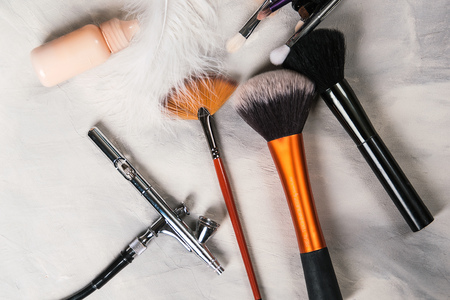 Set of makeup brushes, airbrush and cosmetics on grey concrete background, top view. Makeup tools and accessory, copy space, flat lay. Beauty, fashion and shopping concept Banque d'images - 107135127