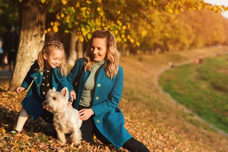 Mother and little daughter walking with dog in autumn. Outdoors portrait of happy family. Autumn fashion. Stylish little daughter and her beautiful mother. Happy childhood Фото со стока