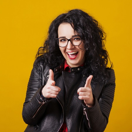 Excited happy woman in eyeglasses. Woman pointing fingers at camera, isolated on yellow. Close up portrait of hipster in glasses. Woman dressed in black leather jacket. Fashion girl pointing on you