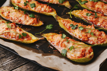 Baked stuffed zucchini boats. Zucchini stuffed with meat, vegetables, cheese and parsley. Healthy food concept. Zucchini boats in a baking tray on table