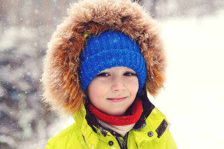 Cute child boy in winter clothes outdoors. Portrait of happy little boy playing under snow. Happy kid on walk during snowfall. Winter holidays. Winter kids fashion. Happy and healthy childhood