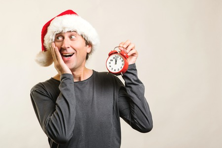 Worried man wearing Santa Claus helper hat. Santa guy holding red clock, isolated on white. Time is coming. New Year and Christmas. Last minute christmas shopping. Christmas holidays. Copy space